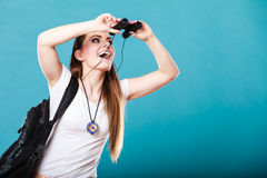 Tourist woman looking through binoculars on blue Royalty Free Stock Photo