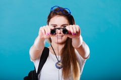 Tourist woman looking through binoculars on blue Royalty Free Stock Images