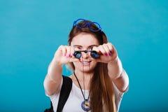 Tourist woman looking through binoculars on blue Royalty Free Stock Photography