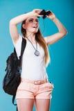 Tourist woman looking through binoculars on blue Royalty Free Stock Photos