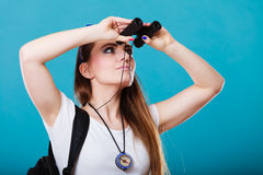Tourist woman looking through binoculars on blue. Summer holidays and tourism concept. Lovely tourist woman with backpack compass looking through binoculars on Royalty Free Stock Images