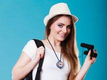 Tourist woman looking through binoculars on blue Royalty Free Stock Images