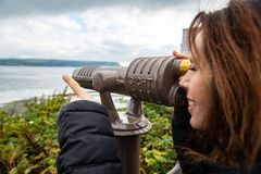 Tourist woman looking through scope at ocean view point stock images