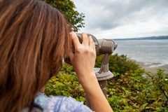 Tourist woman looking through scope at ocean view point stock photography