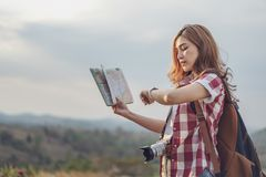 Tourist woman looking a wrist watch and location map. Tourist woman looking at a wrist watch and location map stock image