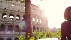Tourist woman looks enchanted the majestic Colosseum of Rome stock video