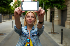 Tourist woman making self portrait with mobile phone digital camera during her vacation holidays in summer. Young female holding smartphone with blank copy space Royalty Free Stock Photography