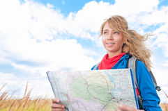 tourist woman with map in summer field. Royalty Free Stock Images