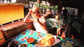 Tourist woman with Mexican cocktail. SLOW MOTION: Happy caucasian woman drinks Margarita, Mexican cocktail of tequila and lime in Mexican restaurant of El Pueblo stock footage