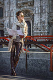 Tourist woman in Milan, Italy with map looking into distance Royalty Free Stock Image