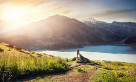 Tourist woman at the mountains at sunrise Stock Images