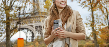 Tourist woman near Eiffel tower with cellphone looking aside Royalty Free Stock Photos