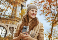 Tourist woman near Eiffel tower with cellphone looking aside Stock Image