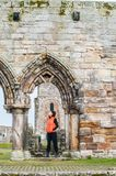 Tourist women observing the ruins of St Andrews. Tourist woman observing the ruins of St Andrews Cathedral , Scotland royalty free stock images