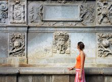 Tourist woman in orange. By the ancient artistic wall Royalty Free Stock Images