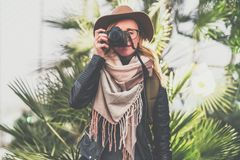Tourist woman photographer in hat and with backpack stands outdoor on background of green plants and takes pictures. Young tourist woman, girl photographer in royalty free stock images