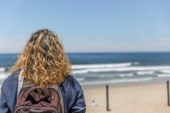 A tourist woman, placidly observes a beach on a sunny day. A tourist woman, placidly observes a beach on a beautiful sunny day stock images