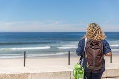 A tourist woman, placidly observes a beach on a sunny day. A tourist woman, placidly observes a beach on a beautiful sunny day stock photos