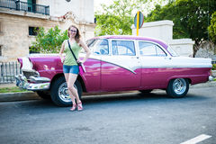 Tourist woman posing next to traditional cuban car, retro americ Royalty Free Stock Photography