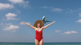 Tourist woman in red swimsuit and hat welcomes airplane for travel. Hello vacation concept stock video