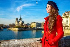 Tourist woman in red trench coat in Paris, France looking aside. Bright in Paris. smiling trendy tourist woman in red trench coat on embankment near Notre Dame Stock Photo