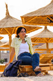 Tourist woman relaxing at sunset on beach Royalty Free Stock Image