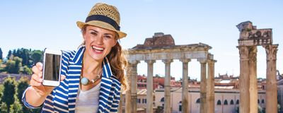 Tourist woman in Rome showing smartphone blank screen Stock Image
