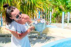 Tourist woman with sea turtle in the hands in exotic reserve Royalty Free Stock Photography