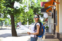 Tourist woman searching direction on location map. Cheerful woman searching direction on location map while traveling abroad in summer, happy female tourist Stock Photography