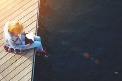 Tourist woman searching information on tablet while relaxing on a pier. Top view shot of a young blonde hair woman sitting on a jetty next to a sea while using Royalty Free Stock Photo