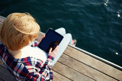 Tourist woman searching information on tablet while relaxing on a pier after walk. Young blonde hair woman sitting on a jetty next to a sea while using busy Stock Photography