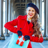 Tourist woman showing shopping bag and Christmas present box Royalty Free Stock Photos