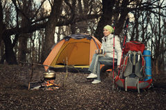 Tourist woman sits at the camp in forest and mountains Royalty Free Stock Photography