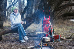 Tourist woman sits at the camp in the forest Stock Photo