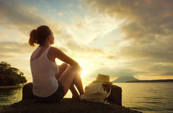 Tourist woman sits and enjoys a spectacular sunset of the island. Rear view of happy young woman backpacker sitting on the pier enjoying stunning sunset stock images