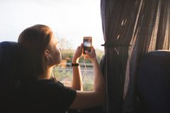 Free Tourist Woman Sits In A Bus Near The Window And Photographs Landscapes At Sunset On A Smartphone Stock Photo - 140991070