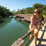 Tourist woman sitting on the bridge over the river Stock Images