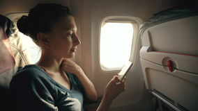 Tourist woman sitting near airplane window at sunset and using mobile phone during flight stock video