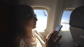 Tourist woman sitting near airplane window at sunset and using mobile phone during flight stock video footage