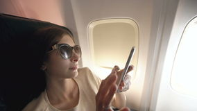 Tourist woman sitting near airplane window at sunset and using mobile phone during flight stock footage