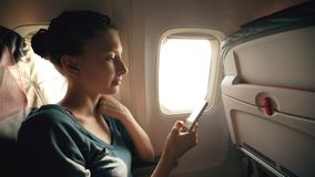 Tourist woman sitting near airplane window at sunset and using mobile phone during flight. In airplane cabin Royalty Free Stock Image