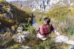 Tourist woman sitting on the top of the  autumn mountain,enjoying the view Stock Image