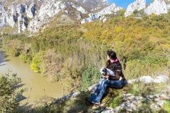 Tourist woman sitting on the top of the  autumn mountain,enjoying the view Royalty Free Stock Photos