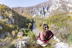Tourist woman sitting on the top of the  autumn mountain,enjoying the view Stock Photography