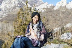 Tourist woman sitting on the top of the mountain,hugging her white dog Royalty Free Stock Image