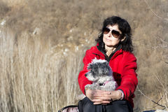 Tourist woman sitting on the top of the mountain,hugging her white dog Royalty Free Stock Photo