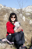 Tourist woman sitting on the top of the mountain,hugging her white dog Stock Photography