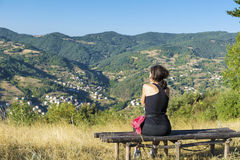 Tourist woman sitting on a wooden bench in a high autumn mountain Royalty Free Stock Photo
