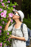 Tourist woman smelling flowers sun glasses Stock Image