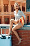 Tourist woman with Spain flag sitting on parapet and looking at. Happy trendy tourist woman with Spain flag and trolley bag sitting on parapet and looking at the royalty free stock images